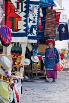 JE_GT_mg_1499.jpg  Central America, Guatemala, Santiago.  Mayan woman walking by textile stalls at market.